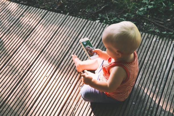 baby halten eines handys und lustige selfie mit einer handy-kamera nehmen. - lustige babybilder stock-fotos und bilder