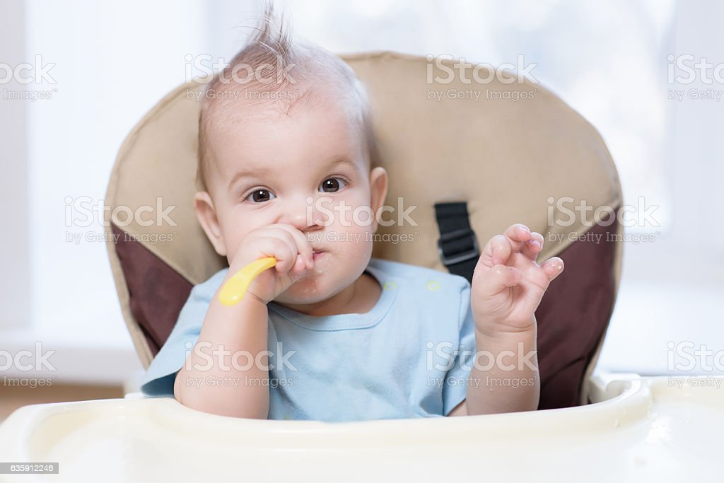 baby holding a spoon in his mouth stock photo