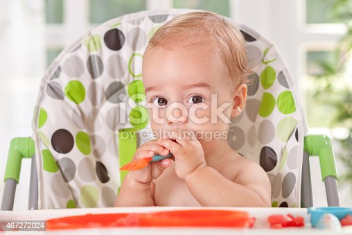 149051793 istock photo Baby holding fork and eating fruit 467272024