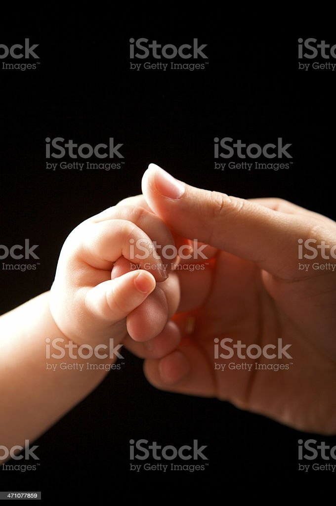 baby holding mother's hand stock photo