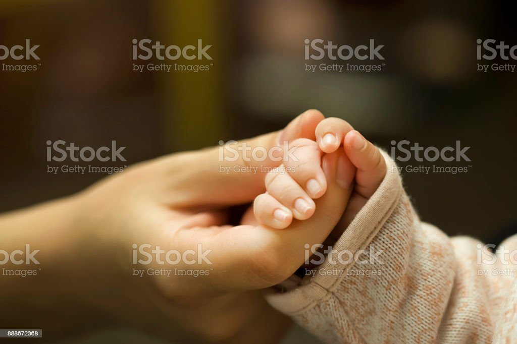 Baby Holding Mothers Hand stock photo