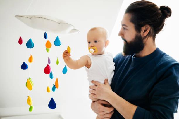 bebê, segurando o pai enquanto estiver jogando wth mobile - mobile - fotografias e filmes do acervo