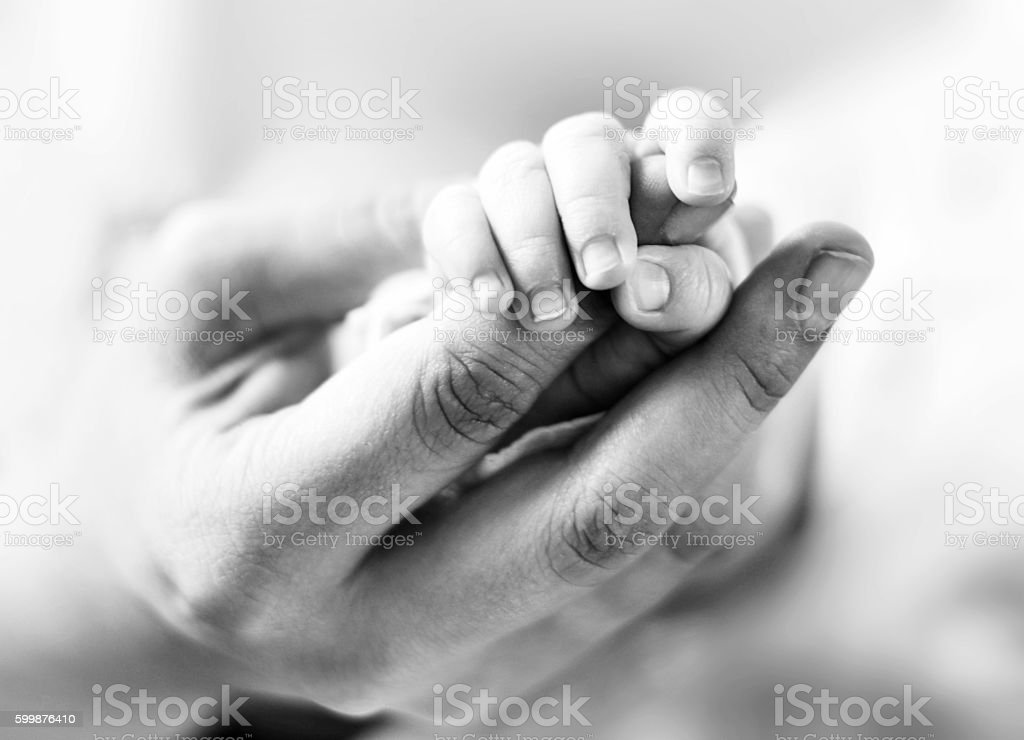 Baby holding the mothers hand stock photo
