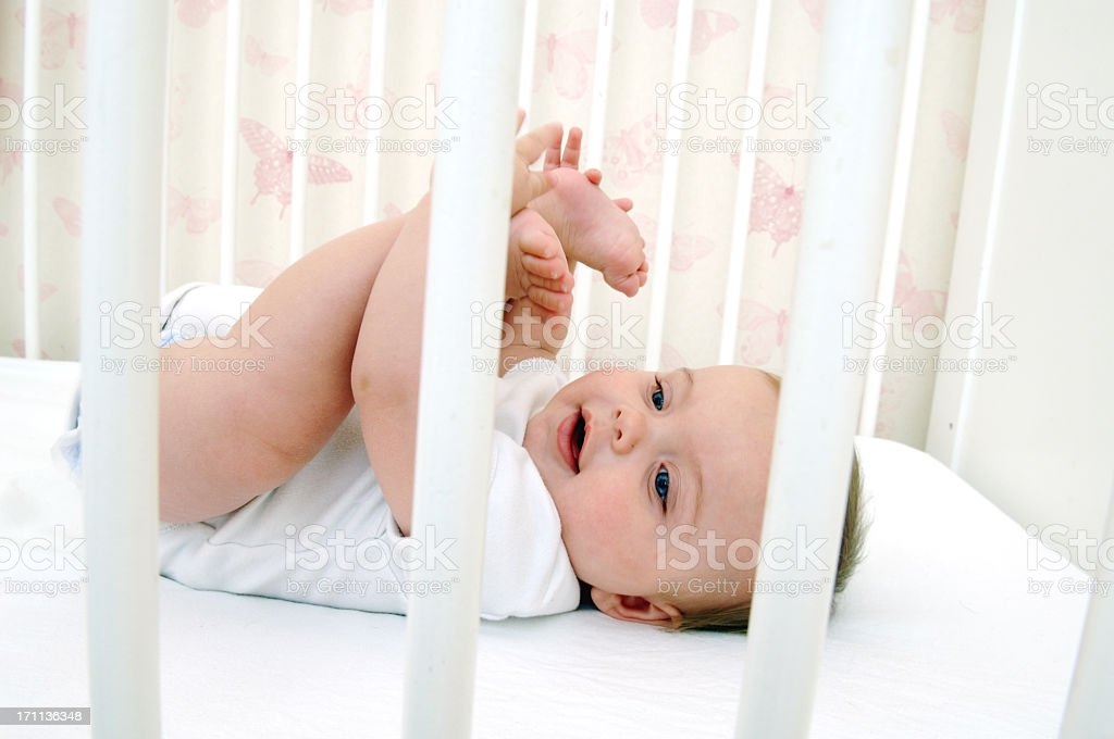 Baby holding their toes while lying in crib stock photo