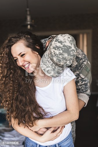 Baby I'm home. Soldier kissing his wife after coming home from war.