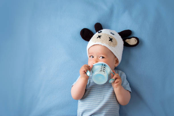 Baby in a cow hat drinking milk stock photo