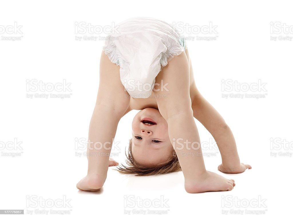 Baby in a diaper standing on his head stock photo