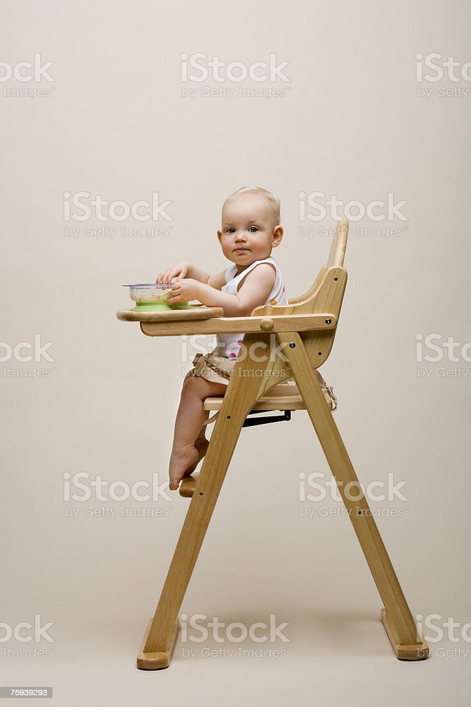Baby in a high chair stock photo