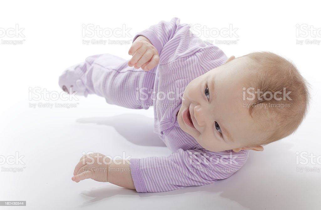 Baby in a purple jumper rolling around stock photo
