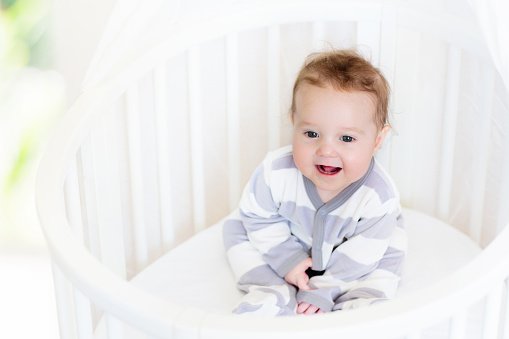 Baby playing in a white crib. Little child in bed. Bedding and furniture for kids nursery. Infant going to sleep. Nap for young kid. Sleepwear for children.