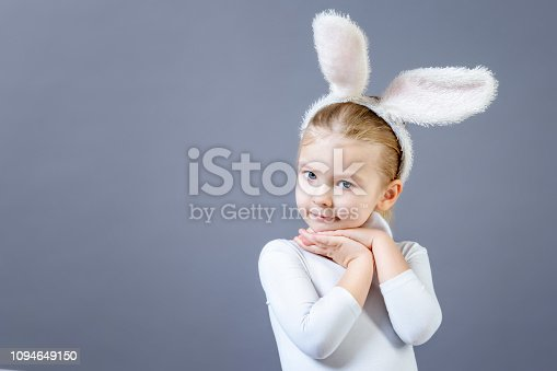 155096501 istock photo Baby in a white rabbit costume on a gray background. Cute little girl with ears of a hare, near copy space. Advertising photo with space for text. 1094649150
