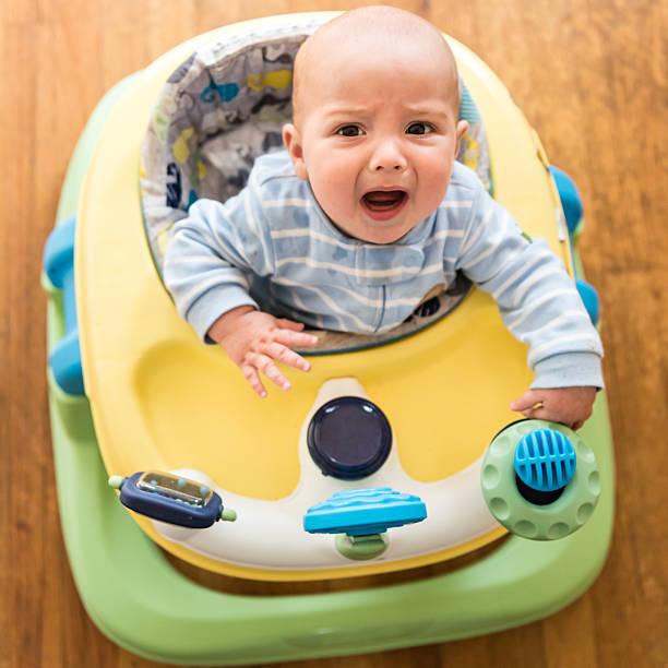 Baby in baby walker stock photo