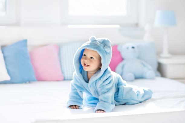 baby bademantel oder handtuch nach bad - badewannenkissen stock-fotos und bilder