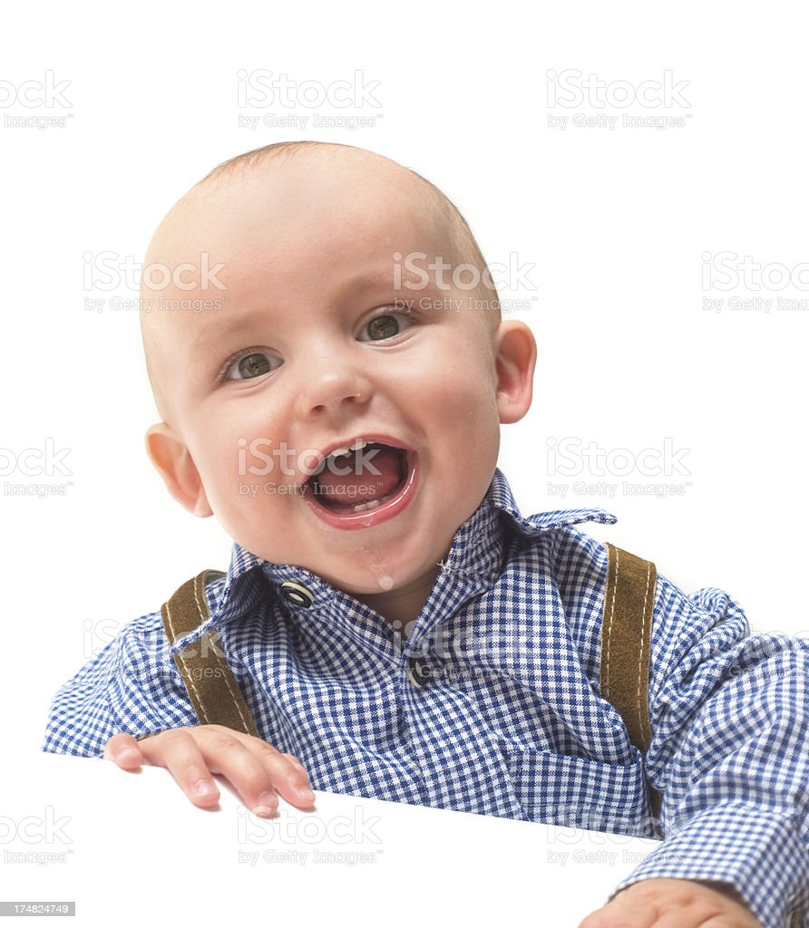 Baby in bavarian clothes looking down and laughing stock photo
