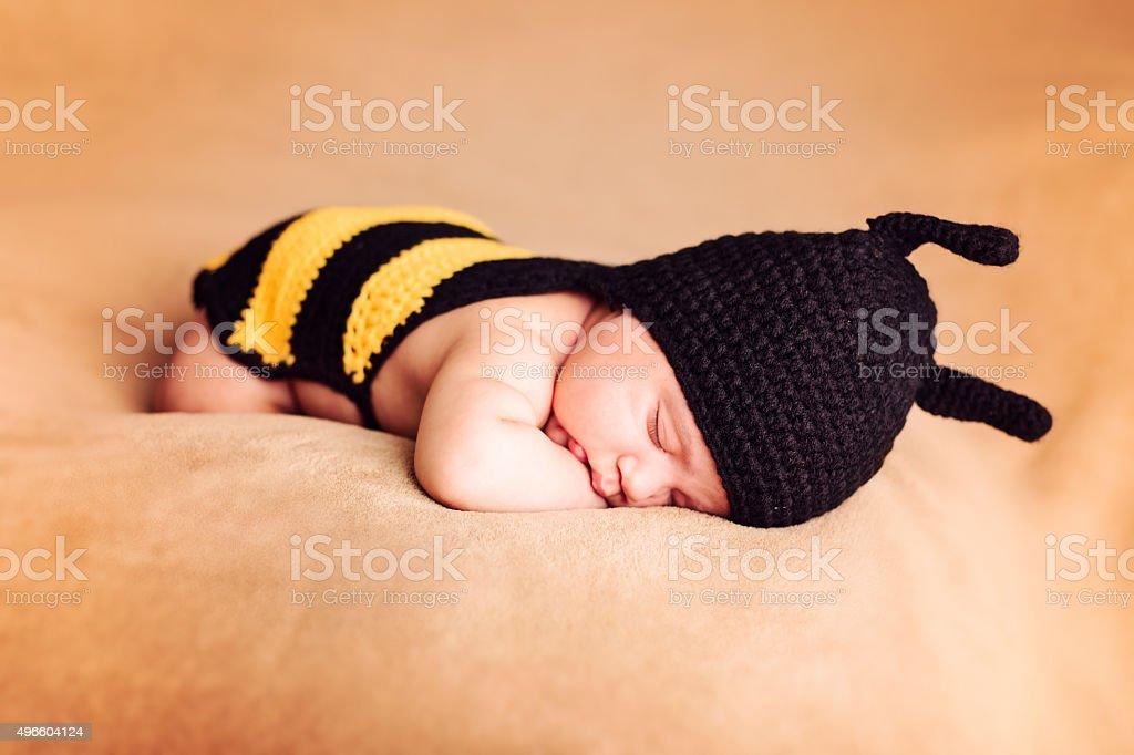 Baby in bee costume sleeping stock photo