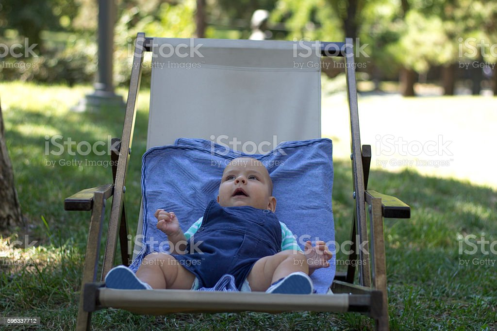 Baby in blue clothes sit in outdoor textile chair. royalty-free stock photo