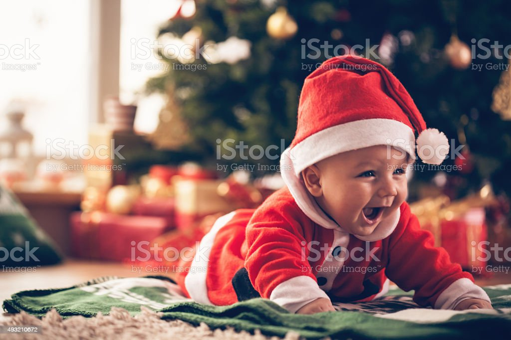 Cute baby luying down on the floor near Christmas tree.