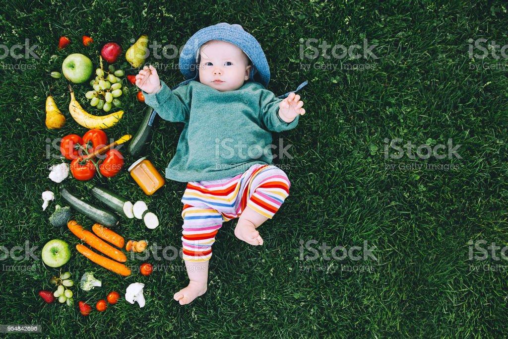 Bebé en colores ropa probar alimentos y marco de diferentes frutas y verduras frescas sobre fondo de hierba verde, vista superior. - foto de stock