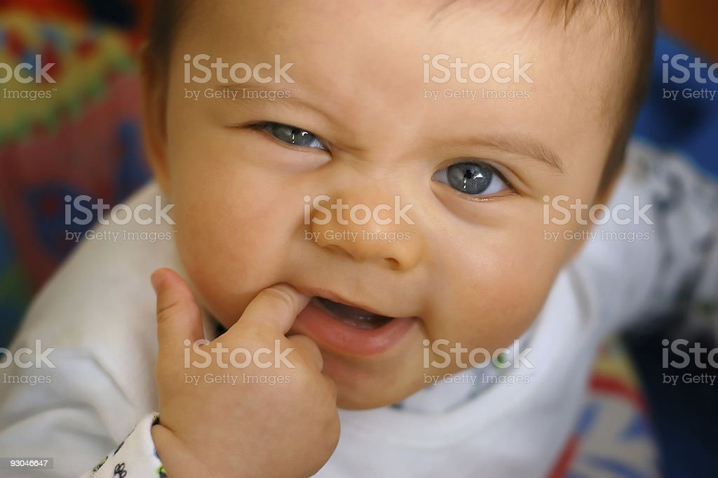 A baby in crib and pajamas teething on finger stock photo
