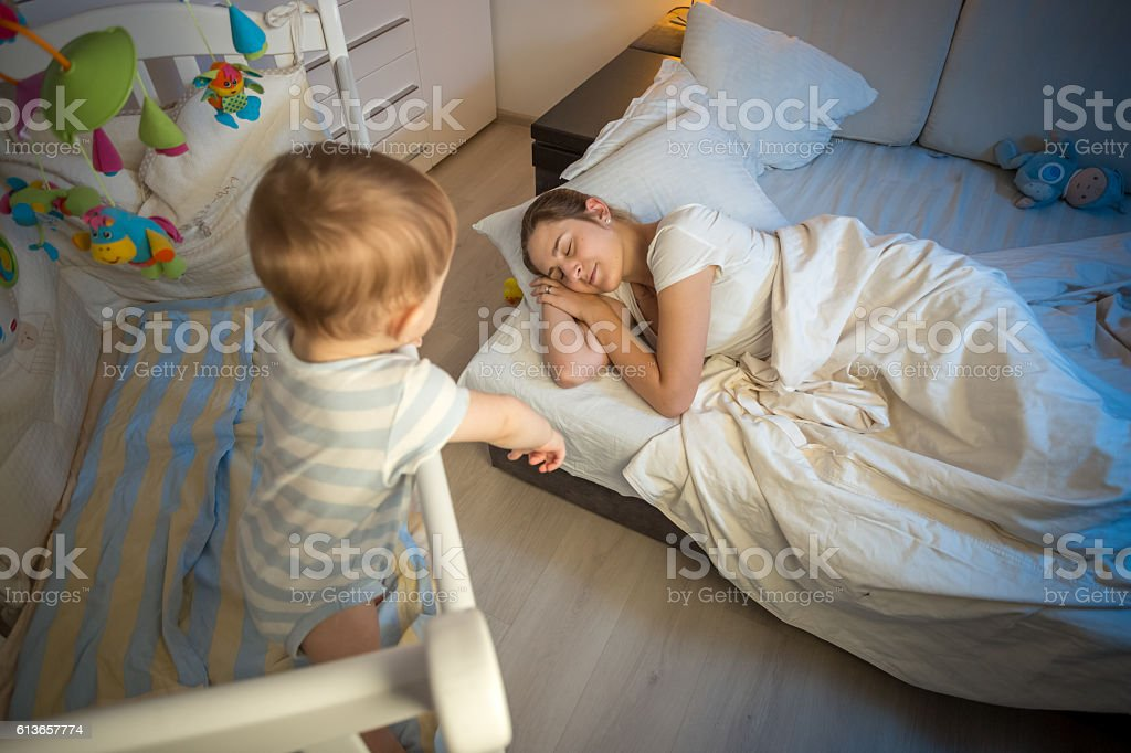 Baby in crib crying and trying to wake up mother stock photo