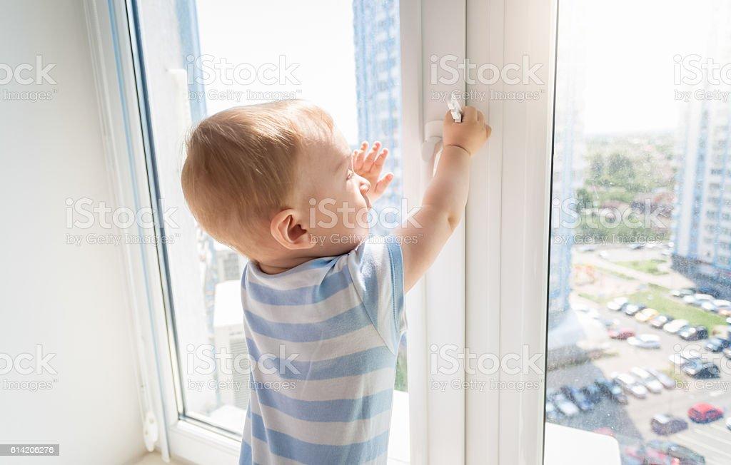 Baby in danger. Baby pulling handle of window stock photo