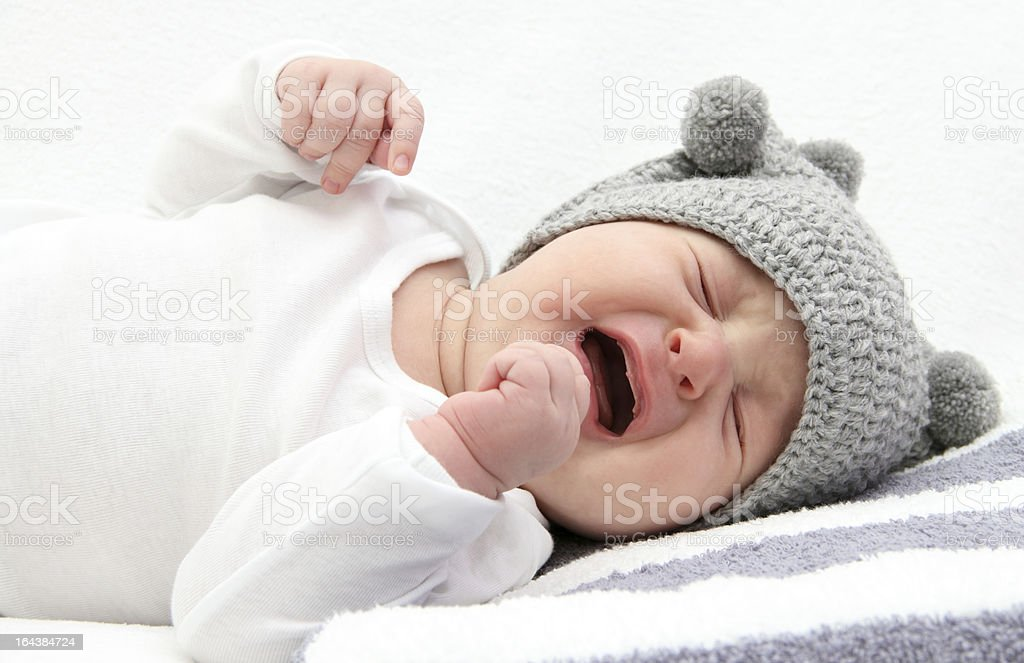 Baby in gray hat and white shirt crying stock photo