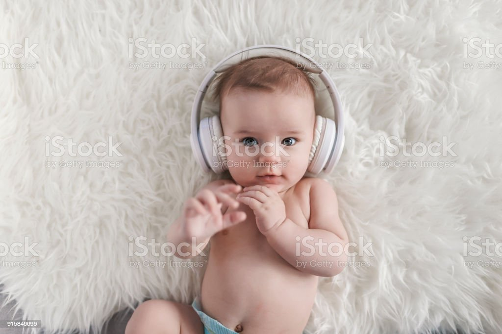 Baby in Headphones Listening to Music stock photo