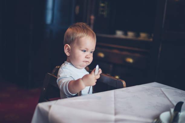 baby im hochstuhl am tisch - kinderstuhl und tisch stock-fotos und bilder