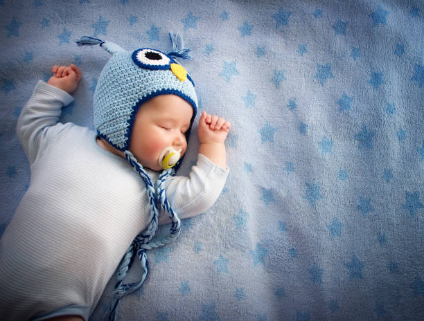 baby in owl hat sleeping stock photo