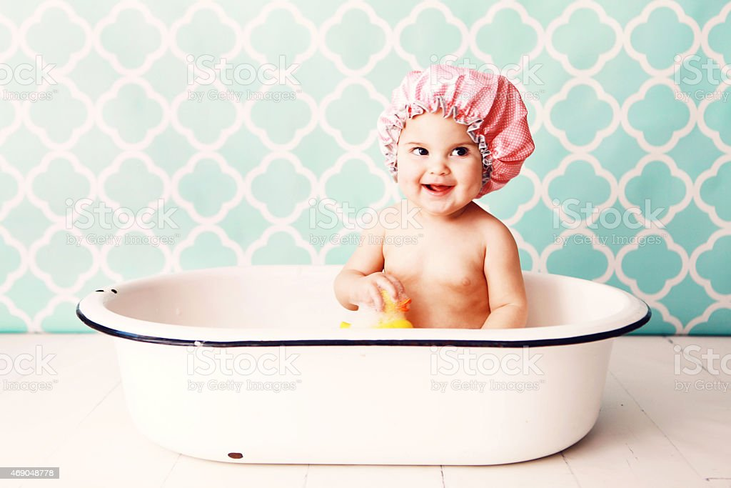 Baby in pink shower cap plays with a rubber duck in the bath stock photo