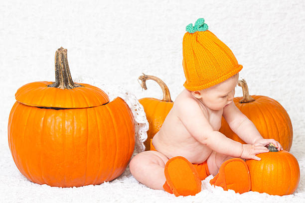 Baby in Pumpkin Hat Sitting near Pumpkins stock photo