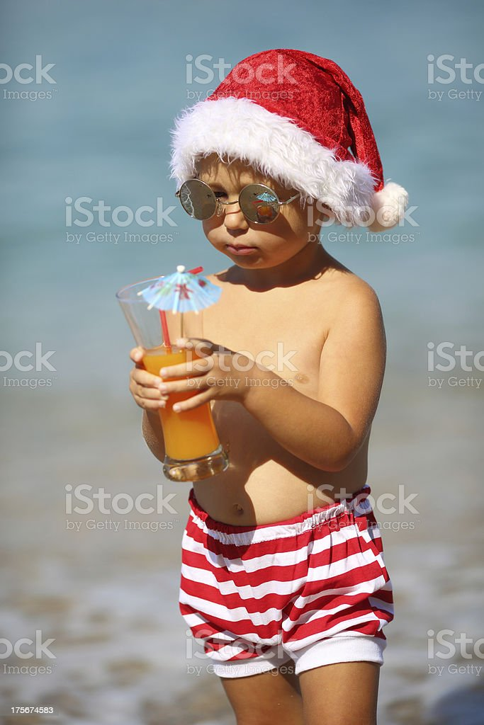 Baby in Santa costume on the beach royalty-free stock photo