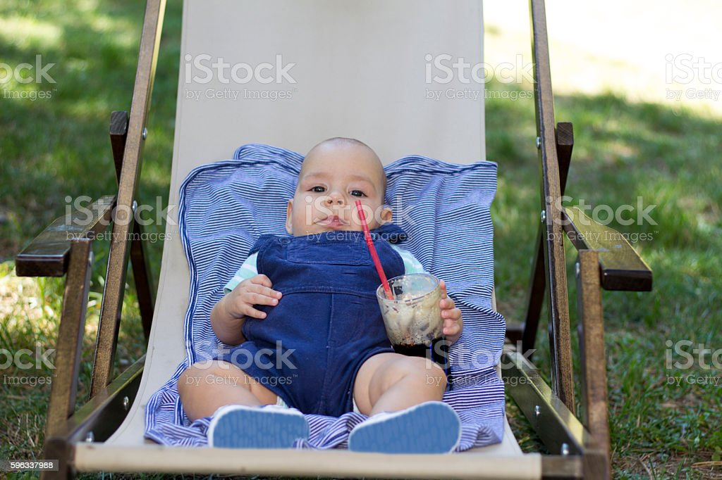 Baby in sit in outdoor textile chair and hold glass. royalty-free stock photo