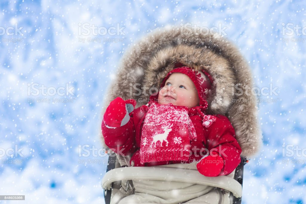 Baby in stroller in winter park with snow stock photo