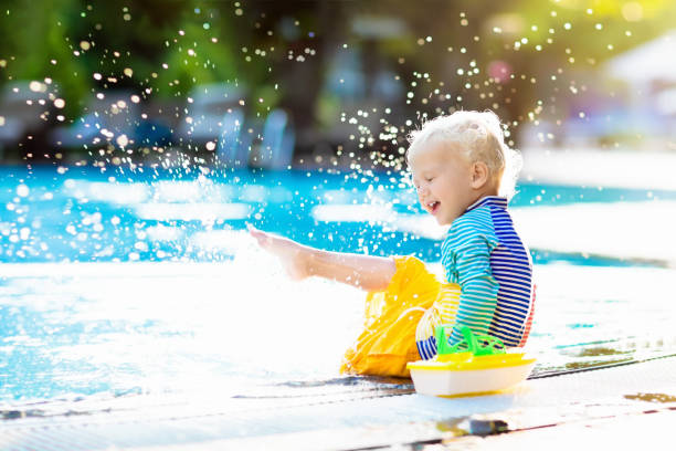 Baby in swimming pool. Family summer vacation. stock photo