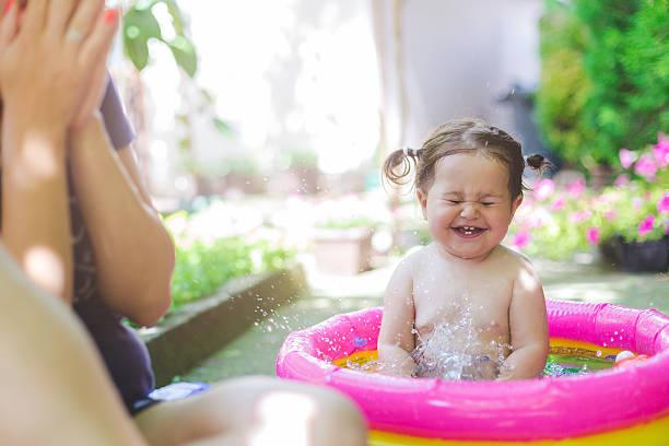 baby in swimwear playing in baby pool - pool schritte stock-fotos und bilder