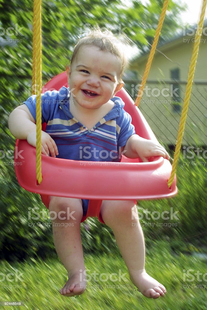 Baby in swing stock photo
