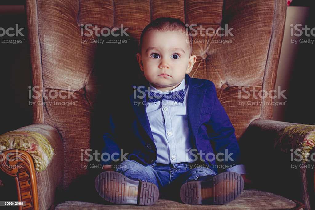 Baby in the clothing business in a business armchair stock photo