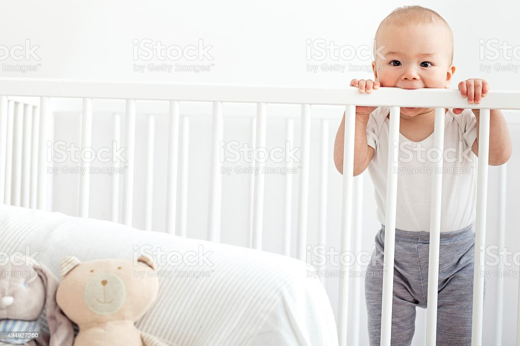 Baby in the crib standing and looking at camera stock photo