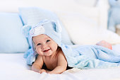 Baby in towel after bath in bed