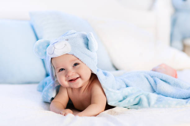 Baby in towel after bath in bed stock photo