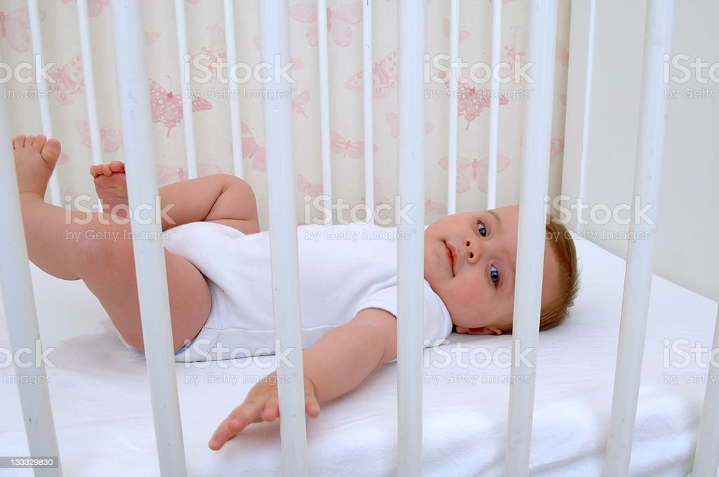 Baby in white lying on back in a white crib stock photo