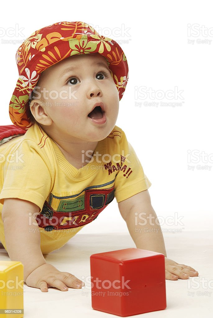 Baby in yellow shirt and red panama looking up sideways - Royaltyfri Aktivitet Bildbanksbilder