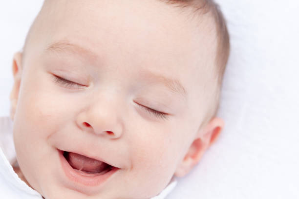 Baby indoors on white laughing with eyes closed stock photo
