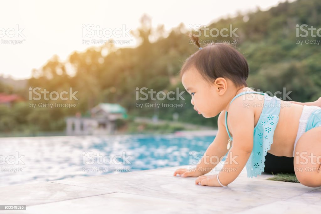 Baby infant tries to crawl down to the pool alone with danger. stock photo