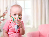 Baby girl making inhalation with mask on her face.Inhaling child.
