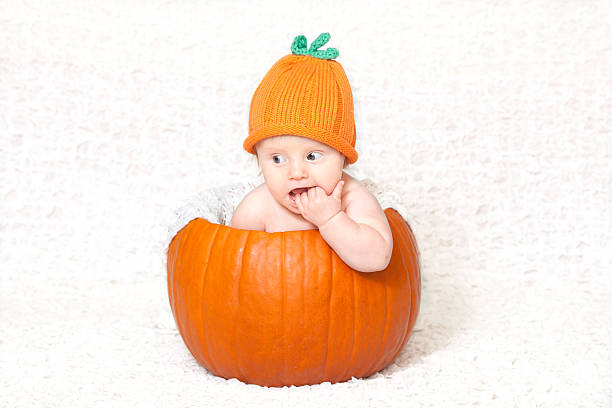 Baby inside pumpkin in pumpkin Halloween hat and costume stock photo
