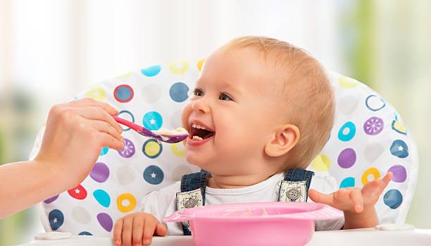 Glückliche Mutter füttert lustige baby mit Löffel – Foto
