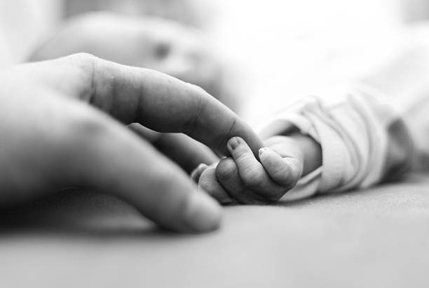 Baby is holding father's finger for the first time stock photo