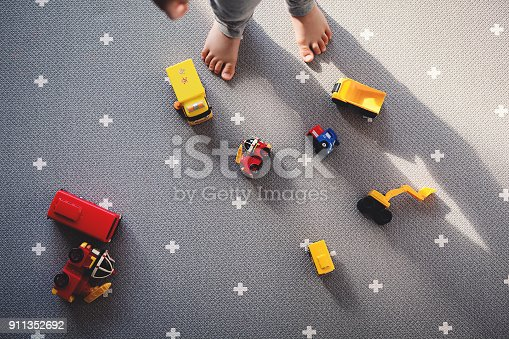 istock baby is looking down floor with car toys. a boy is playing lonely alone 911352692